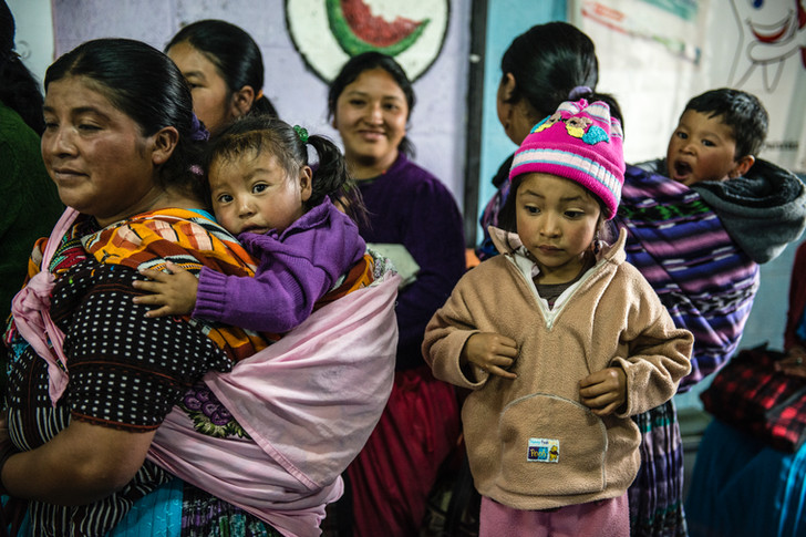 Mothers waiting in line to receive nutrition supplements for her children.