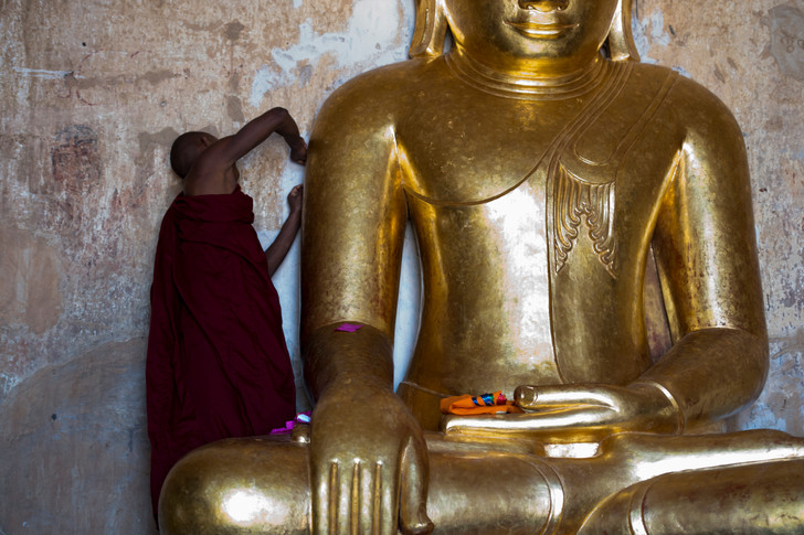 A monk plating the buddha statue with gold leaf.