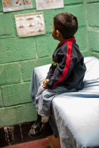 Child waiting on the exam table at the Primeros Pasos clinic.