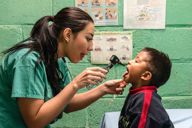 Zoe, a volunteer nurse, examines a child.
