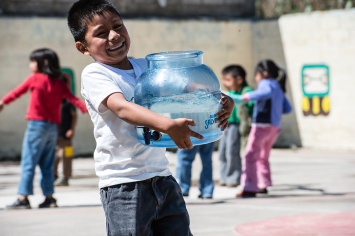 Child carrying water for science activity.