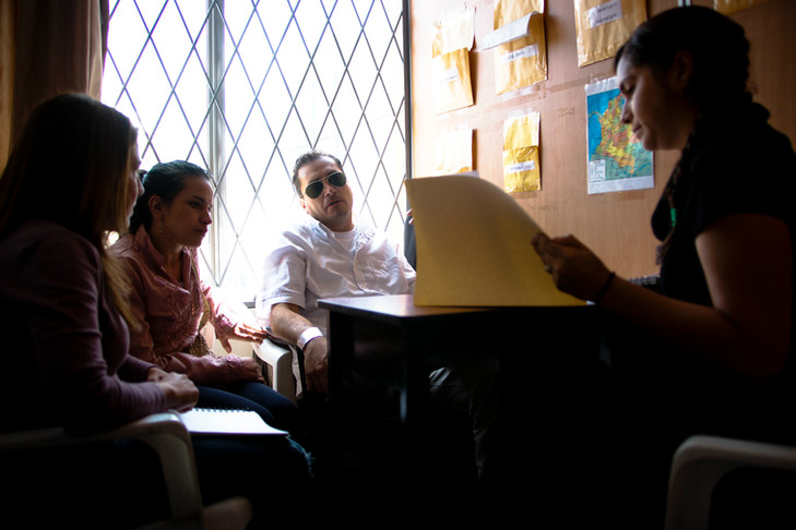 A refugee couple receiving consult regarding their legal status from a volunteer legal advocate in Quito.