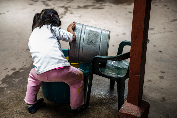 A girl filling up a bowl to wash hands. This day care has no running water.