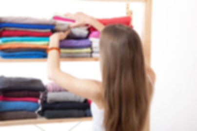 A young woman stacks clean folded clothes on a shelf.
