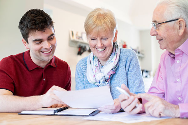 Young man helping his senior parents with financial paperwork
