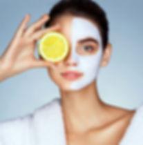Lovely girl holding a slice of lemon in