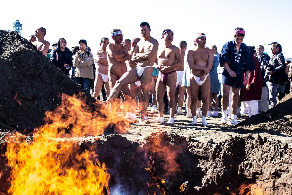 Antes de entrar na água, os participantes se aquecem em fogueiras ao som dos tambores japoneses.