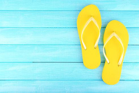 Bright flip-flops on color wooden background.jpg