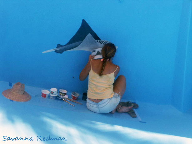 Savanna Redman painting a sting ray mural in a swimming pool