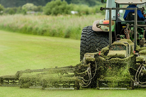 A tractor being used to cut grass at a c