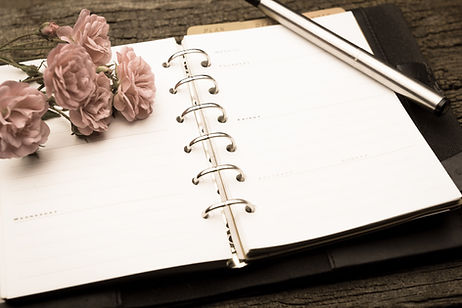 An open planner calendar with flowers and a pen resting on top
