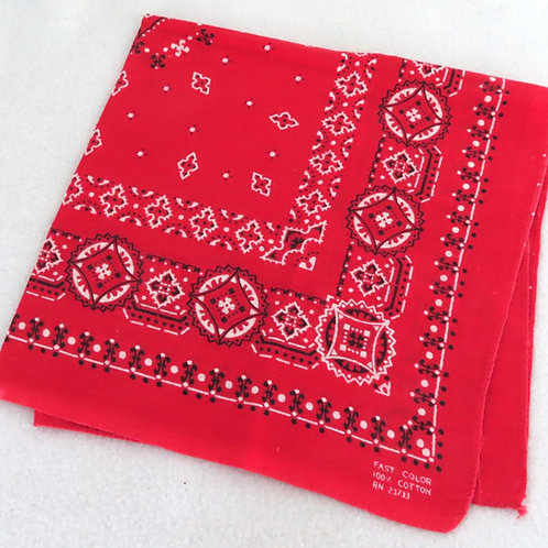 Vintage red bandana with black and white allover design, folded into a square