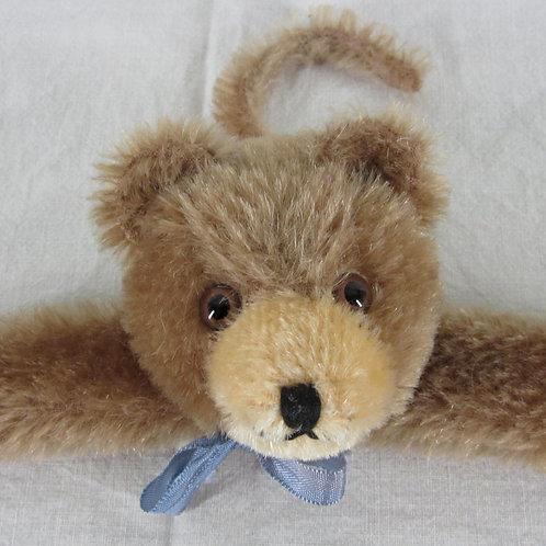 Closeup cute vintage fuzzy mohair teddy bear clothes hanger with blue ribbon bow