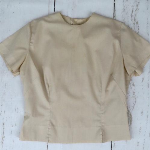Vintage beige short sleeved suit blouse pictured against a gray backdrop