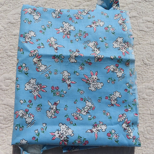 Vintage blue fabric with white cartoonish bunnies with daisy flowers.
