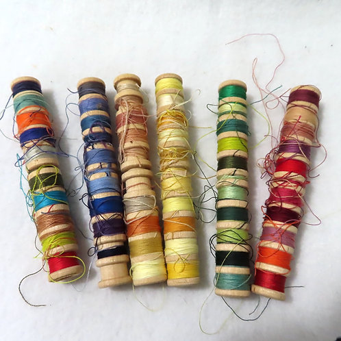 Colorful assortment of mending thread on long wood bobbins