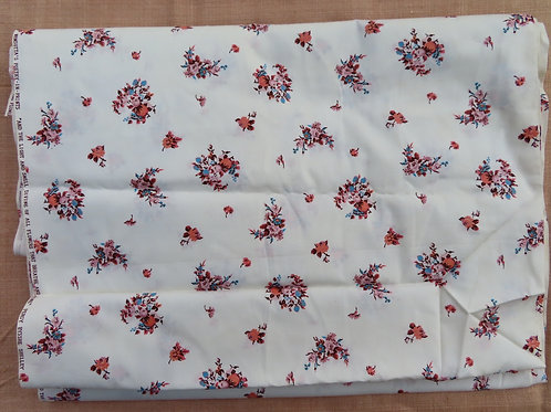 White cotton floral fabric has pink sprays of flowers
