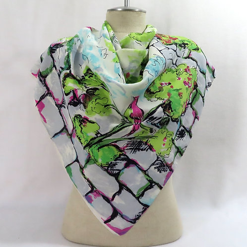 Vintage scarf shown on mannequin, with brick wall and scenic print.