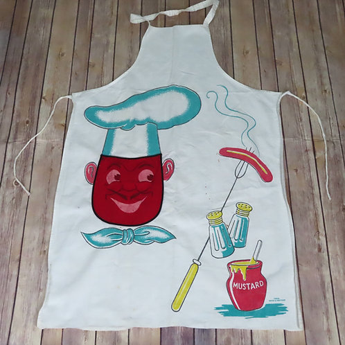 vintage 50s BBQ apron with red faced chef wearing a hat, and hot dogs on a 3-tined fork