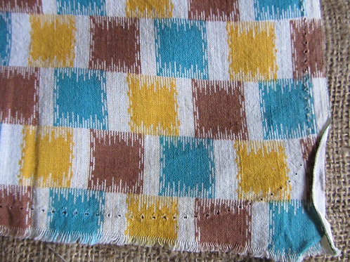 White fabric with brown, yellow and blue geometric print