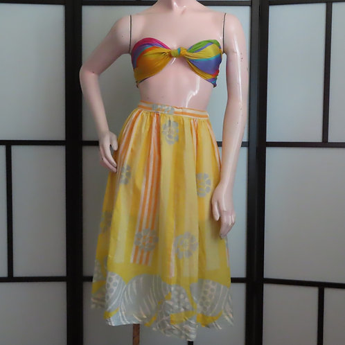 Woman mannequin wearing yellow print skirt and bright scarf halter top