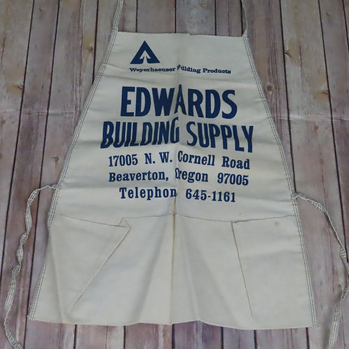 White canvas apron with promotional text at the chest in blue print