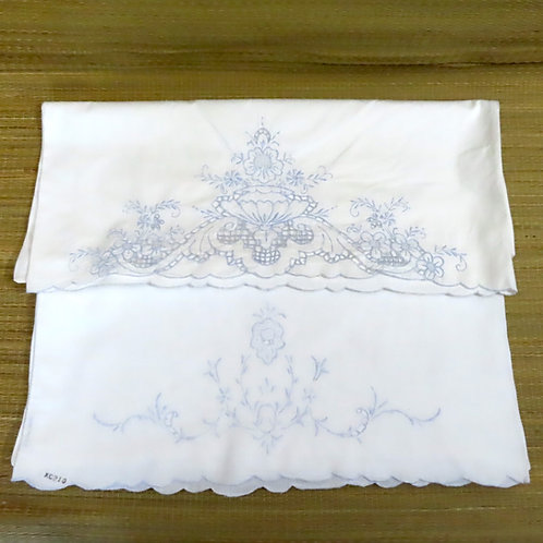 Pair of white cotton pillowcases, each with delicate blue embroidery