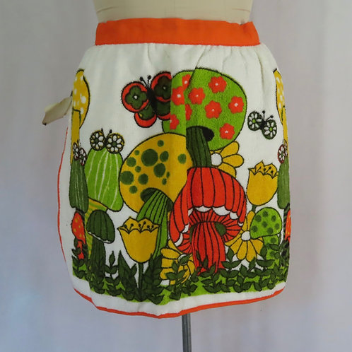 Vintage waist apron from the 60s or 70s with a bold colored mushroom, butterfly and flowers graphic.