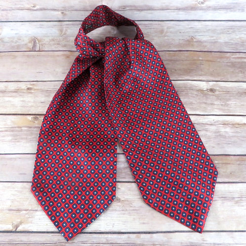Red foulard print ascot laying on wooden table