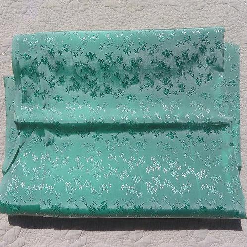 Aqua green shiny fabric with shamrock flower weave