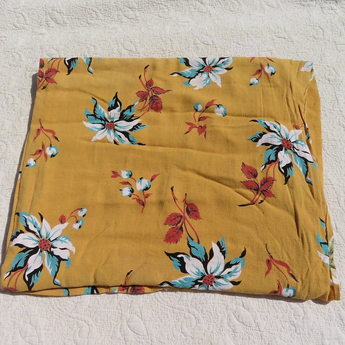 Vintage golden yellow fabric with large teal green, white and red floral print.