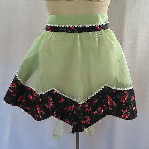 Green vintage apron with black rosebud floral print trim at the waist and shaped hem