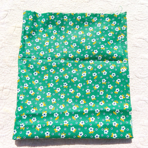 Grass green fabric covered with small white and yellow flower print.