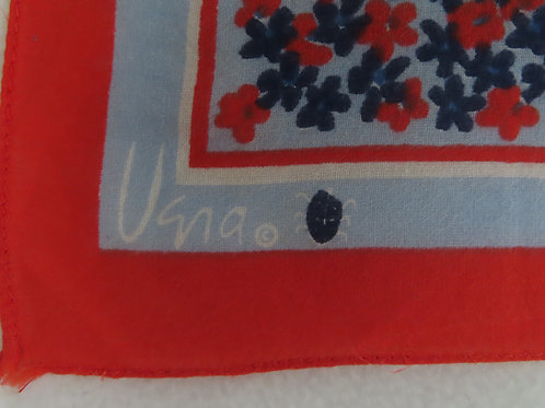 Corner of red and blue floral print bandana marked with Vera and a ladybug