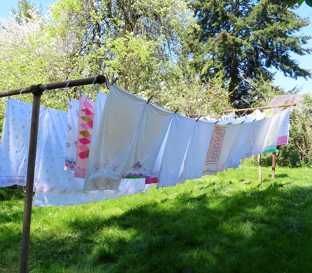 Vintage pillowcases on a clothesline in my backyard with trees and grass