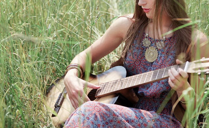 young hippie woman with guitar performs