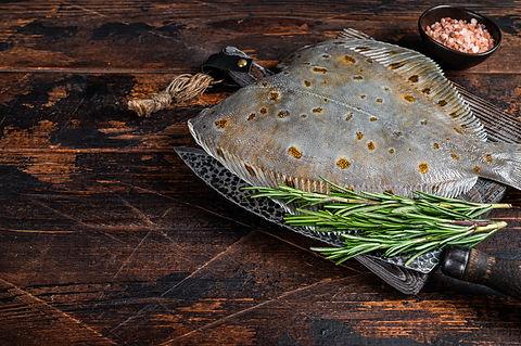 Raw plaice flatfish fish on butcher boar