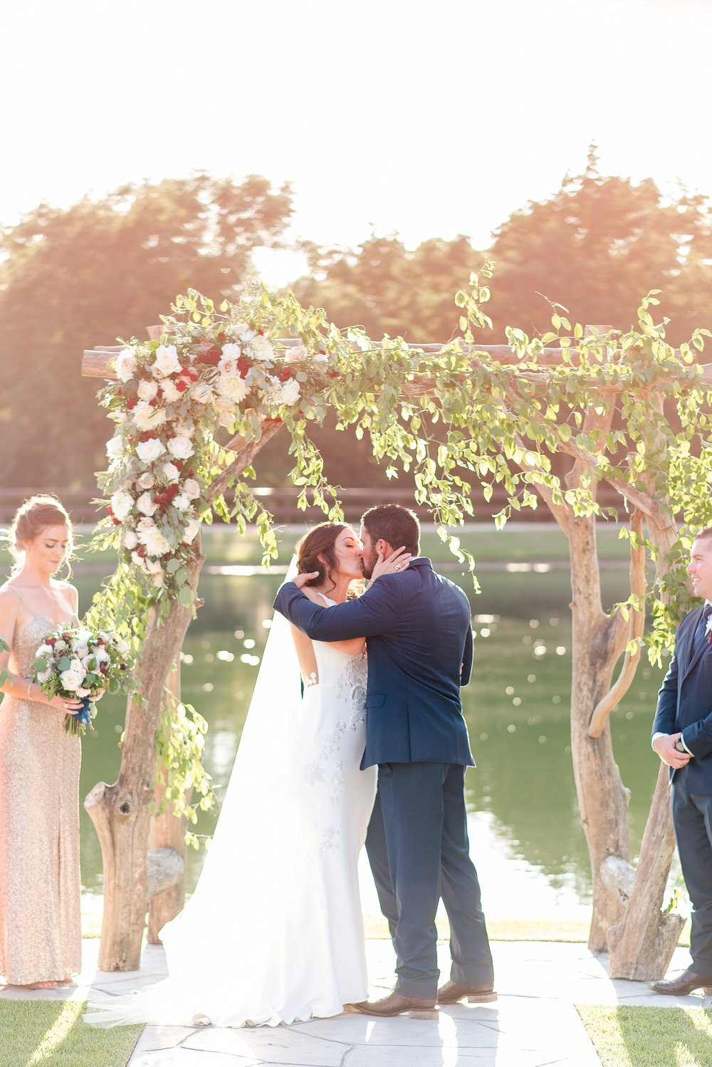 The newlyweds share a kiss in the sunshine beaming through the flowing greenery and blooms.
