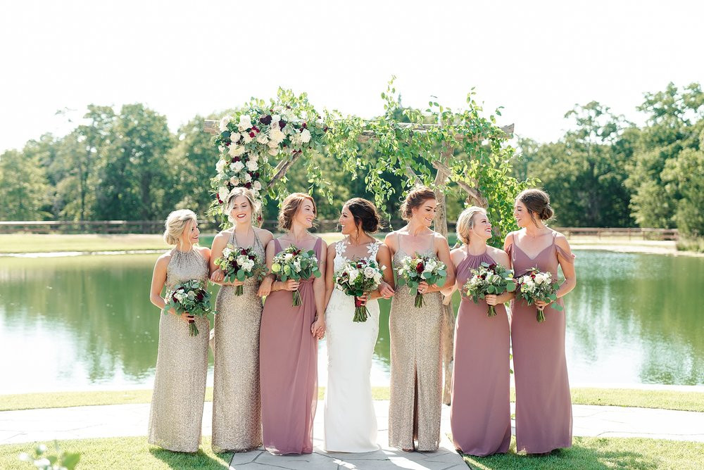 The stunning bride and her bridesmaids stand under the floral arch with their bouquets. The creamy whites and deep maroon of the bouquets pair seamlessly with the gold and mauve bridesmaid gowns and elegant wedding dress.