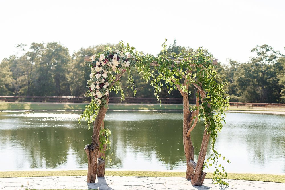 The arch and side floral arrangement stand tall in front of the lake.