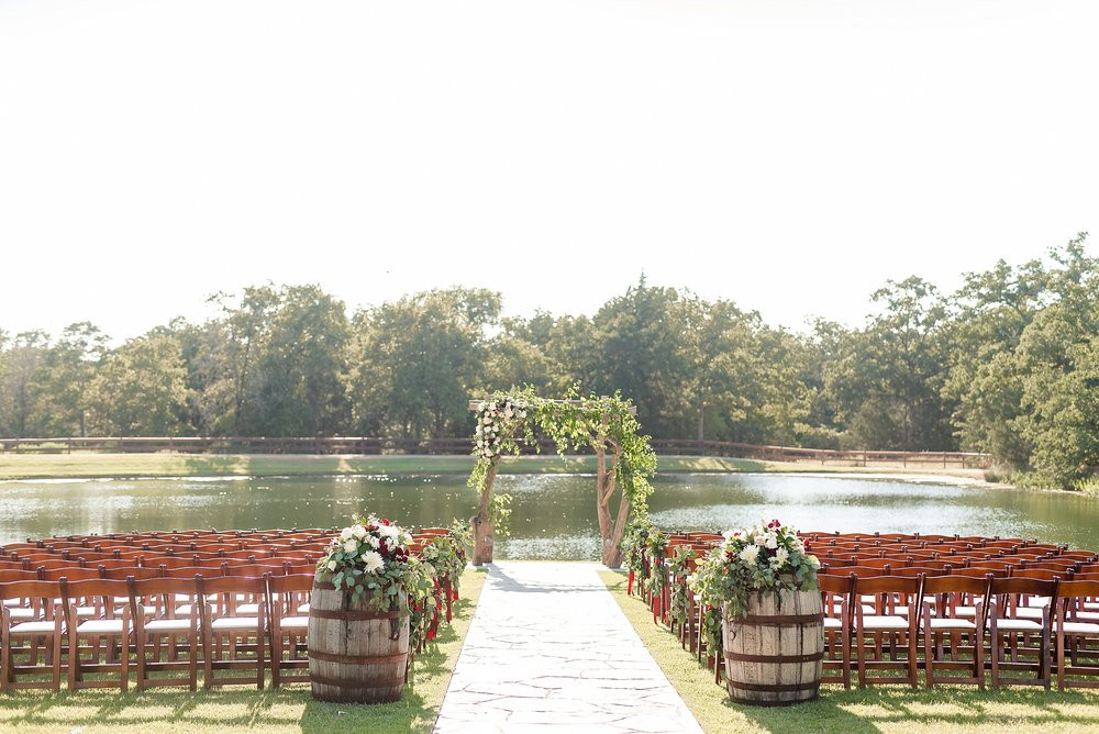 This photo captures the lush green ceremony site with the arch and wine barrel arrangements as focal points.