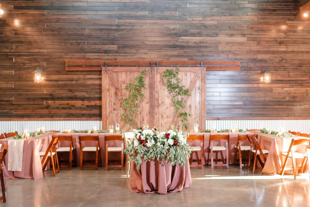 The sweetheart table featuring draping greenery paired with maroon and white flowers. Additional flowing greenery on the barn doors creates an ethereal rustic look.