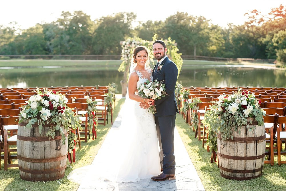 The smiling couple stands between two flourishing barrel arrangements with a picturesque arch and waterfront background.