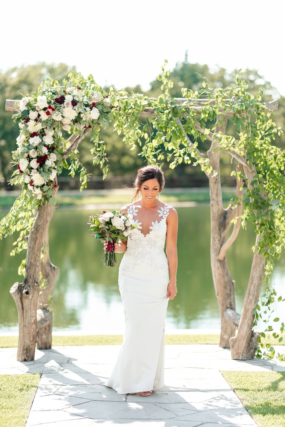 The bride stands holding her bridal bouquet under the arch. The colors she chose are undeniably fitting for an Aggie bride!