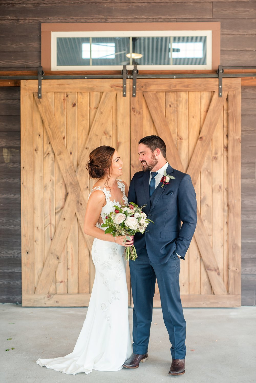 The couple looks lovingly at each other in front of Peach Creek's iconic barn doors.