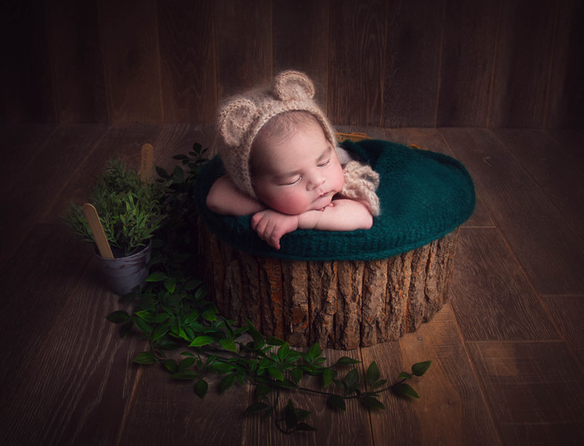 Baby boy posed in a newborn prop