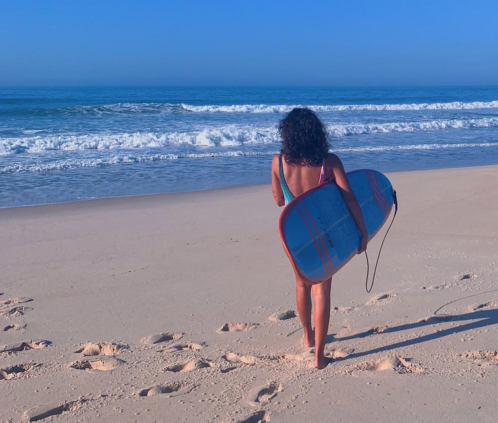 Menina com prancha de surf indo surfar no Grumari