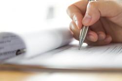 Hånd med penn skriver på papir