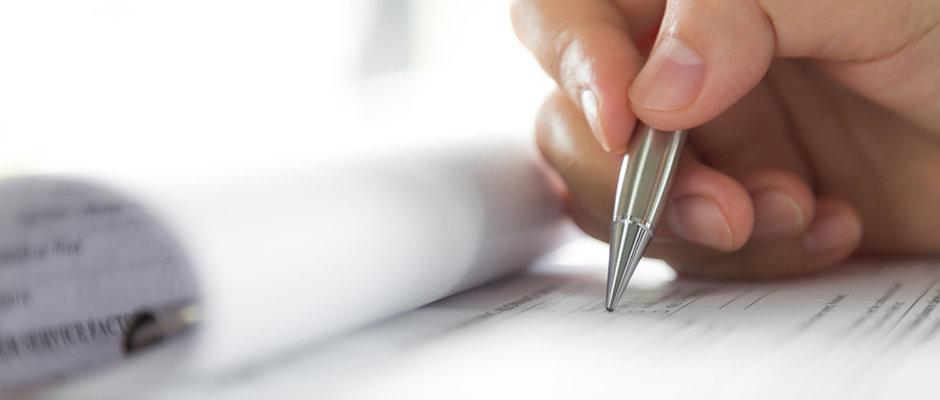 Hånd med penn fyller ut søknad
