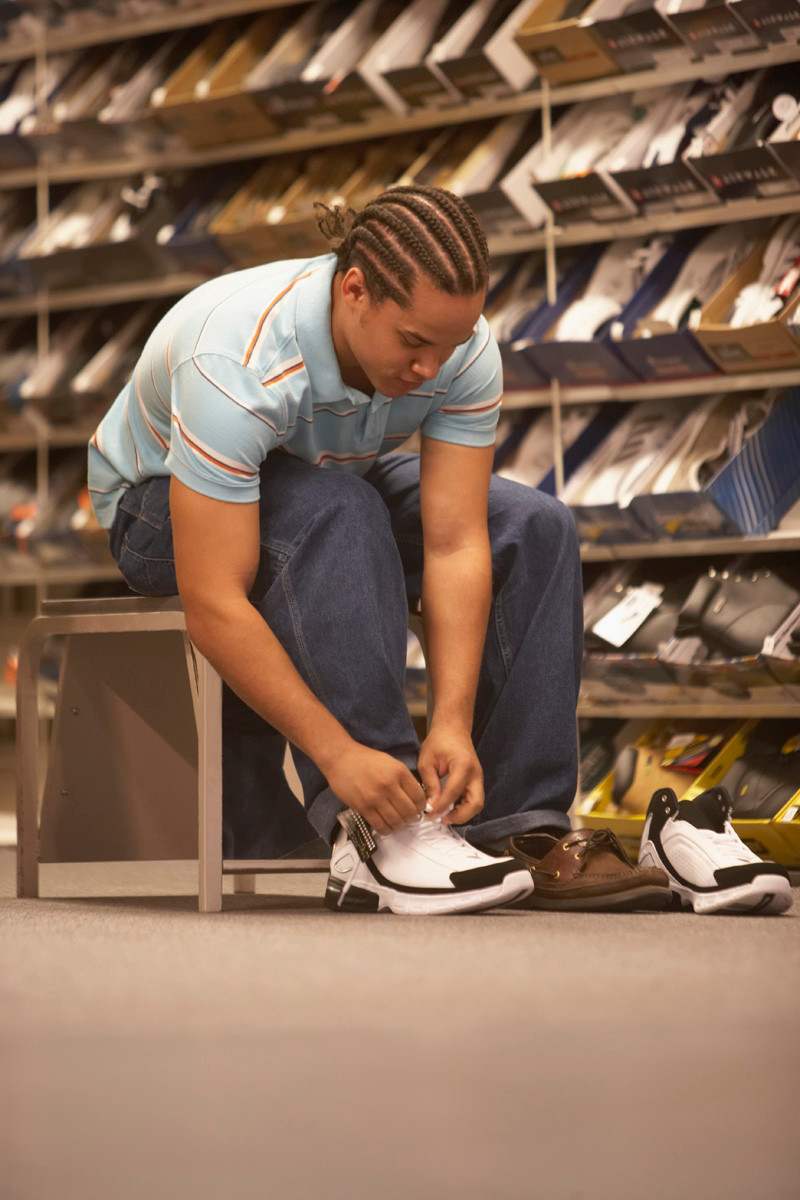 African American young male tying an athletic shoe in a shoe store.